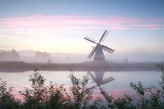 Windmühle durch Fluss bei nebelhaftem Sonnenaufgang Stockbild