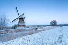 Windmühle durch Fluss und Winterwiese im Schnee Lizenzfreie Stockbilder