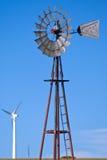 Windmühle für Viehwasser gegen Windturbinen stockbild