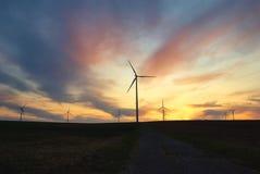 Windmühle nannte Windpark bei dem Sonnenuntergang mit drastischem Himmel Stockbilder