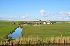 Windmühle reflektierte sich in einem blauen Kanal an einem Sommertag stockbild
