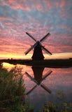Windmühle und drastischer Sonnenaufganghimmel reflektierten sich im Fluss Lizenzfreie Stockfotos