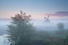 Windmühle und Fluss bei nebelhaftem Sonnenaufgang Stockfotografie