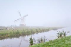 Windmühle und Schafe durch Fluss im Nebel Stockfoto