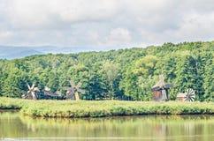 Windmühle und watermill nahe Wassersee, grüner Wald Stockfotos