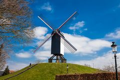 Windmühle unter einem schönen blauen Winterhimmel kurz vor Frühling an der historischen Brügge-Stadt lizenzfreies stockfoto