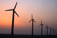 Windmühlen in einer Reihe während der Dämmerung. Stockfotos