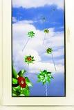Windmühlen im Fenster in Bezug auf den Himmel mit weißen Wolken Lizenzfreie Stockfotos