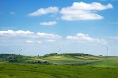Windmühlen zwischen Bauernhoffeld stockfoto