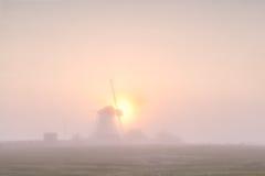 Windmühlenschattenbild im dichten Nebel bei Sonnenaufgang Lizenzfreie Stockbilder