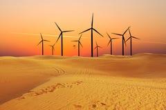 Windm?hlen, die alternative gr?ne Energie im Sandnachtisch erzeugen stockbild