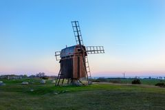 Windmill in Öland Sweden. Old wooden windomill on the countryside of Öland Sweden in the evening with the horizon in the background royalty free stock photos