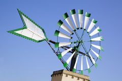 Windmill. Isolated white and green windmill in Majorca with a blue sky as background Royalty Free Stock Images