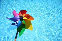 Windmill. Rainbow windmill by the pool Stock Photography