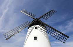 Windmill. White windmill with black sails against blue sky Stock Image