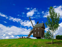 Windmill. Wooden windmill against the summer blue sky with white clouds on a green hill with a birch Stock Photos