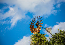 Windmill against blue sky and clouds. Rusted windmill against blue sky and clouds Stock Photo