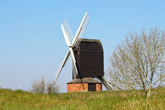 Windmill against a Blue Sky. English wooden Post Mill Windmill against a Blue Sky stock photos
