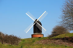 Windmill against a Blue Sky. English wooden Post Mill Village Windmill in against a Blue Sky royalty free stock images