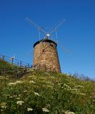 Windmill against brilliant blue sky. Field on wild flowers leading to the hill with the windmill on it against the blue sky. This is an ancient local attraction royalty free stock images