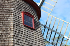 Windmill against sky. Weathered wood shingled and red trim windmill against a blue sky Royalty Free Stock Photo