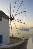 Windmill against sunset and cruise ship Stock Photo