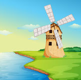 A windmill along the river Royalty Free Stock Images