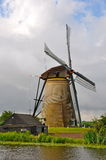 Windmill in Amsterdam. Working Windmill in Amsterdam set along a moving river Stock Image