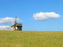 Windmill behind the hill and cloud. Pirogovo, Ukraine Royalty Free Stock Photo