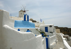 Windmill and blue building on Santorini Island. Royalty Free Stock Image