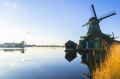 Windmill by a blue clear lake in summer Royalty Free Stock Images