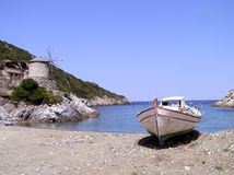 Windmill and boat in Greece. An old windmill and a boat ashore, on a small beach in Greece Stock Photo