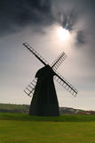 Windmill in Brighton. An interesting shot of a windmill at Rottingdean near Brighton and sun emerging from the cloud royalty free stock photography