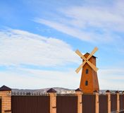 Windmill and brown fence on a blue sky background Stock Photography