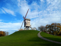 Windmill in Bruges. A windmill on the top of a hill with blue sky and green grass Stock Image