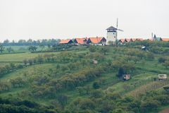 Windmill in Bukovany, southern Moravia, Czech republic. A windmill stands on top of a hill surrounded by farms and a vineyard on a hillside. Moravia, Czech royalty free stock image