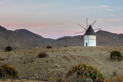 Windmill in Cabo de Gata National Park. Traditional windmill in stone landscape with mountains in the background stock photo