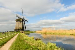 Windmill on canal in West Friesland, Netherlands. West Friesland, Netherlands-April 22, 2015:  Windmill reflected in a canal on a cloudy and sunny day in West Stock Images