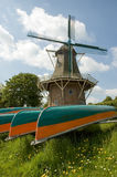 Windmill with canoes. Dutch windmill at the channel Reitdiep in Groningen, The Netherlands Royalty Free Stock Photography