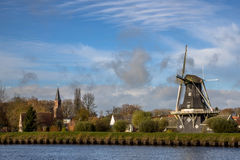 Windmill and church in small village of Woltersum. View of historic wooden windmill and chirch in the small village of Woltersum from the water in the Province Royalty Free Stock Image