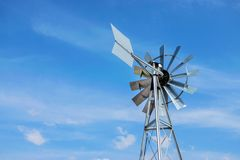 Windmill close up of a and blue sky background. Metal wind turbine with weather vane. Wind energy - old school metal windmill. Against blue sky with copyspace royalty free stock image