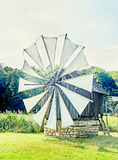 Windmill close up, green forest, wild vegetation Stock Photo