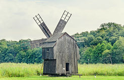 Windmill close up, green forest, wild vegetation Stock Images