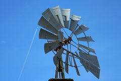 Windmill close-up, jet. Kansas windmill closeup; jet and contrail; old and new technology Stock Photos