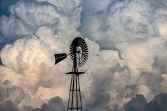 Windmill and clouds. A windmill silhouetted against building storm clouds Royalty Free Stock Photography