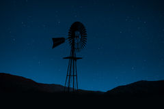 Windmill silhouetted against night sky Royalty Free Stock Photo