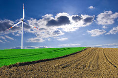Windmill conceptual image. Windmill on the green and plowed field Stock Photos