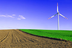 Windmill conceptual image. Windmill on the green and plowed field Royalty Free Stock Photo