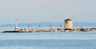 Windmill on sea wall, Corfu, Greece Royalty Free Stock Photos