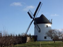Windmill in the countryside. A picture of a four-bladed windmill in the countryside. The windmill is attached to a circular building with a cone-shaped roof stock photo